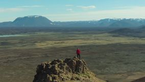 Man Traveler Stands on Mountain Top. Iceland. Aerial View. Man Traveler Stands on Mountain Top in Hverir Area on Sunny Day. Iceland. Aerial View. Drone is stock video footage