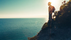 Man traveler stands on the top and enjoys seascape during sunset Royalty Free Stock Photos