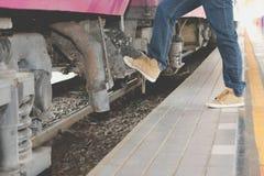 Man traveler stepping up train at railway station. backpacker tr. Man traveler stepping up train at railway station. male backpacker travel alone. Journey on Royalty Free Stock Photos