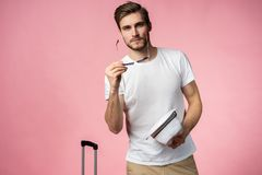 Man traveler with suitcase, passport and ticket on color background. stock image