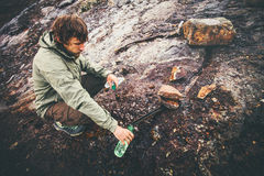 Man Traveler taking mineral water in bottle from natural well Stock Photos