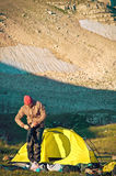 Man Traveler with Tent Camping arranging hiking equipment Royalty Free Stock Image
