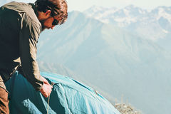Man Traveler with tent camping equipment at mountains outdoor Stock Image