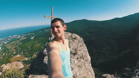 Man traveler at the top of a rocky mountain with Cross smiles, rejoices and rotates the camera around him. Man traveler at the top of a rocky mountain with Cross stock footage