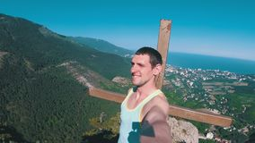 Man traveler at the top of a rocky mountain with Cross smiles, rejoices and rotates the camera around him. Man traveler at the top of a rocky mountain with Cross stock video footage