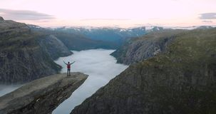 Man traveler on Trolltunga rocky cliff with backpack. Hiking in Norway mountains Travel Lifestyle success adventure concept vacations outdoor above clouds stock footage