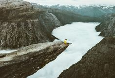 Man traveler on Trolltunga rocky cliff edge in Norway. Mountains Travel Lifestyle adventure emotional concept extreme vacations outdoor above clouds tourist Royalty Free Stock Images