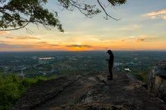 Man traveler is using digital phone on cliff Royalty Free Stock Photos