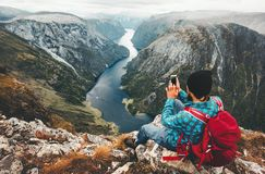 Man traveler using smartphone sitting on mountain summit. Travel in Norway adventure lifestyle active vacations modern technology connection concept Stock Photo