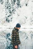Man Traveler walking alone lake and forest winter Stock Photo
