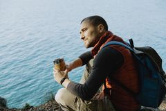 Man traveler wearing a sports vest sits on a mountain with a bac Royalty Free Stock Photos