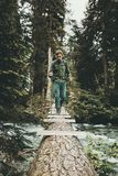 Man Traveler into the wild forest crossing river on log bridge royalty free stock photos