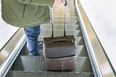 Man traveling by airplane. Hand of the passenger with luggage on the escalator at the airport. Man traveling by airplane. Hand of the passenger with luggage on Royalty Free Stock Image