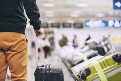 Man in airport terminal. Man traveling by airplane. Young passenger holding his suitcase near baggage claim in airport terminal Stock Photo