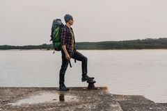 Man Traveling Backpack. Enjoying the beautiful view of the lake Royalty Free Stock Images