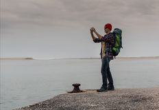 Man Traveling Backpack. Enjoying the beautiful view of the lake Stock Photography