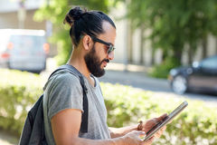 Man traveling with backpack and tablet pc in city Stock Images