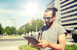 Man traveling with backpack and tablet pc in city. Travel, tourism, backpacking, technology and people concept - man traveling with backpack and tablet pc Royalty Free Stock Photos
