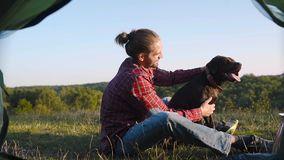 Man traveling with dog, camping in nature. Man traveling with dog, sitting near camping tent and enjoying vacation in nature stock video footage