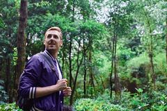 Man traveling in the forest with backpack. Young smiling man wearing the purple blazer is walking in the forest with gray backpack royalty free stock image