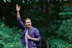 Man traveling in the forest with backpack. Young smiling man wearing the purple blazer is walking in the forest with gray backpack royalty free stock photos