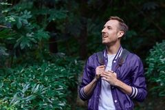Man traveling in the forest with backpack. Young smiling man wearing the purple blazer is walking in the forest with gray backpack holding his jacket royalty free stock images