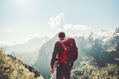 Man traveling in mountains Travel Lifestyle. Concept adventure active summer vacations wayfaring outdoor hiking sport with red backpack Stock Image