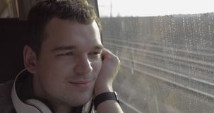 Man traveling by train and enjoying outside view. Young man with headphones traveling by rail. He enjoying view from the train window with thoughtful look stock video footage