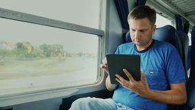 A man is traveling on a train. Sits by the window, uses a digital tablet. Device on the road. HD video stock video