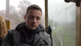 Man traveling by tram and sleep.
