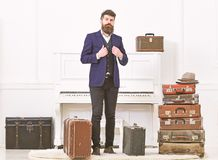 Man, traveller with beard and mustache with luggage, luxury white interior background. Macho elegant on strict face. Stands near pile of vintage suitcase, ready stock image
