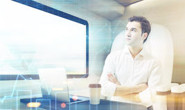 Man travelling in train compartment with graphs. Young man travelling in a modern train. Laptop and coffee cup are standing on the compartment table. Concept of royalty free stock image