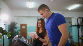 Man on treadmill in gym Girl on the treadmill trainer, sports a healthy lifestyle stock footage