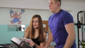 A man on a treadmill. Young man and woman instructor working out on a treadmill in a fitness club stock footage
