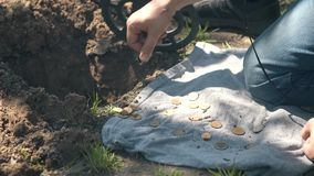Man treasure hunter takes out of the ground found coins. Man treasure hunter with a metal detector takes out the found coins from the ground close up stock video