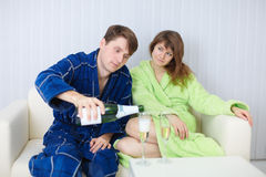 Man treats lady with champagne, at home on sofa Royalty Free Stock Photo
