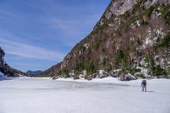 Man trecking across a frozen lake Stock Photo