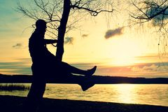Man on tree. Silhouette of  lone man sit on branch of birch tree at sunset at shoreline. Man on tree. Silhouette of  lone man sit on branch of birch tree  in Stock Photography