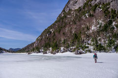 Man trekking across a frozen lake Stock Images