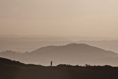 Man trekking on a mountain with a hazy pink background. Lone man trekking in the distance on a mountain in India against a range of mountains shown in a pink Stock Photos