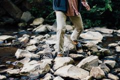 Man Trekking Rocky Stream during Daytime Stock Photo