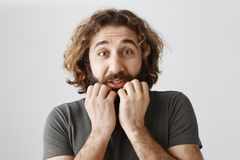 Man trembling from fear. Indoor shot of scared adult bearded guy with curly hair holding hands on jaw, waiting for scary. Moment in film, shaking and being Stock Photos