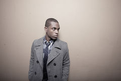 Man in a trench coat glancing over shoulder Stock Photo