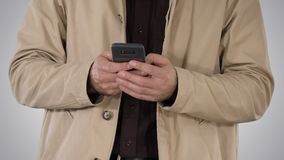 Man in trench coat using mobile smart phone on gradient background. Medium shot. Man in trench coat using mobile smart phone on gradient background stock photo