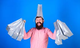 Man with trendy beard wearing pink shirt and silver bag on his head isolated on blue background. Shopping champion. Winning first prize in contest, happiness Royalty Free Stock Image