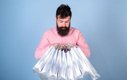 Man with trendy hairstyle and beard holding silver bags. Hipster in pink shirt with curious look isolated on blue royalty free stock photos