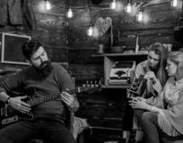 Man with trendy hipster beard composing song, music concept. Bearded man playing guitar. Family spending time listening. Man with trendy hipster beard composing stock photography