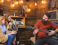 Man with trendy hipster beard composing song, music concept. Bearded man playing guitar. Family spending time listening royalty free stock image