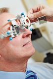 Man with trial frame at optician. Elderly men with trial frame and trial glasses at optician stock photos