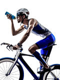 Man triathlon iron man athlete cyclist bicycling drinking. Man triathlon iron man athlete biker cyclist bicycling biking drinking in silhouette on white Royalty Free Stock Photos